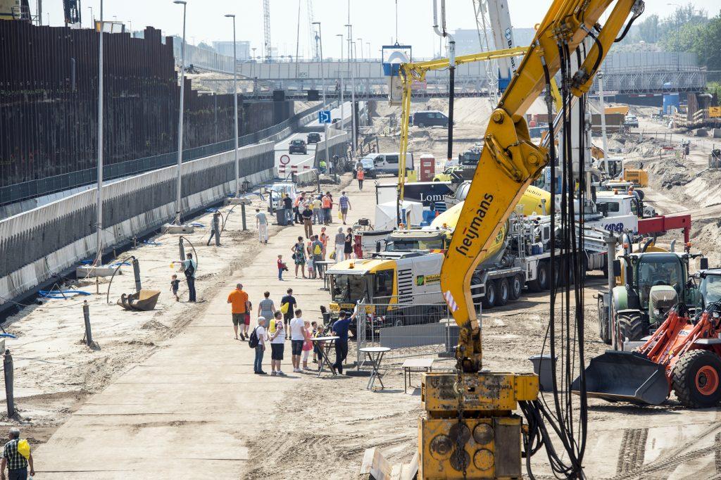 Foto van het bouwterrein van de Gaasperdammertunnel, tientallen mensen lopen over het terrein om dingen te bekijken.